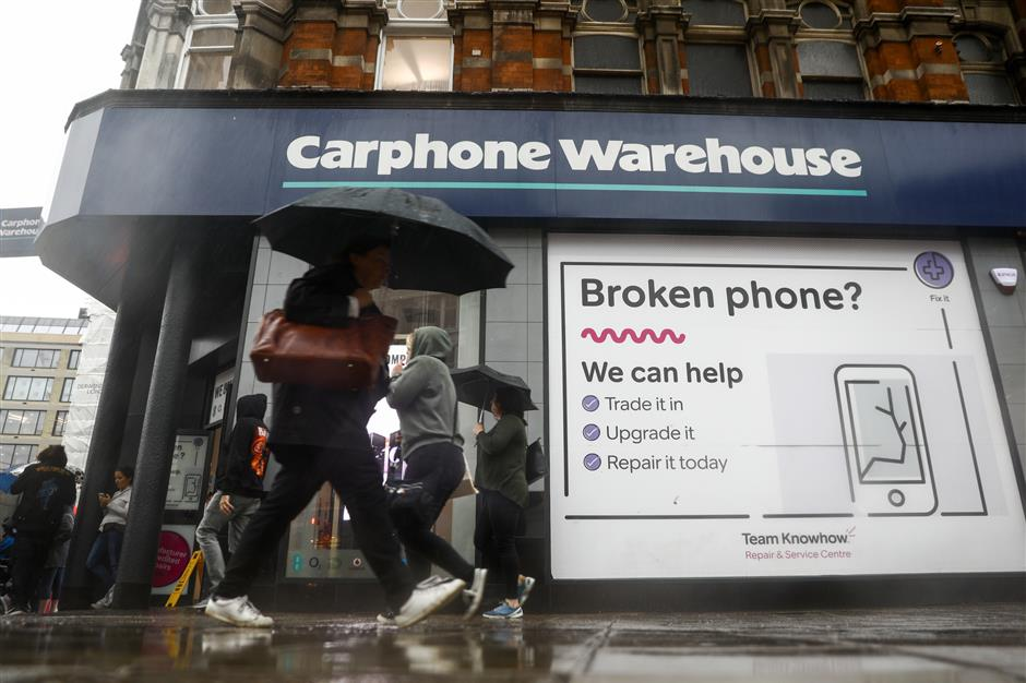 Pedestrians use umbrellas to shelter from the rain as the pass a Carphone Warehouse retail store, operated by Dixonsu00a0Carphoneu00a0Plc, in central London, U.K., on Tuesday, May 29, 2018. Dixonsu00a0Carphoneu00a0Plcu00a0shares plunged the most in nine months after the retailer forecast that earnings this year will slump about 21 percent as it closes mobile-phone stores in a contracting U.K. household-electronics market. Photographer: Simon Dawson/Bloomberg
