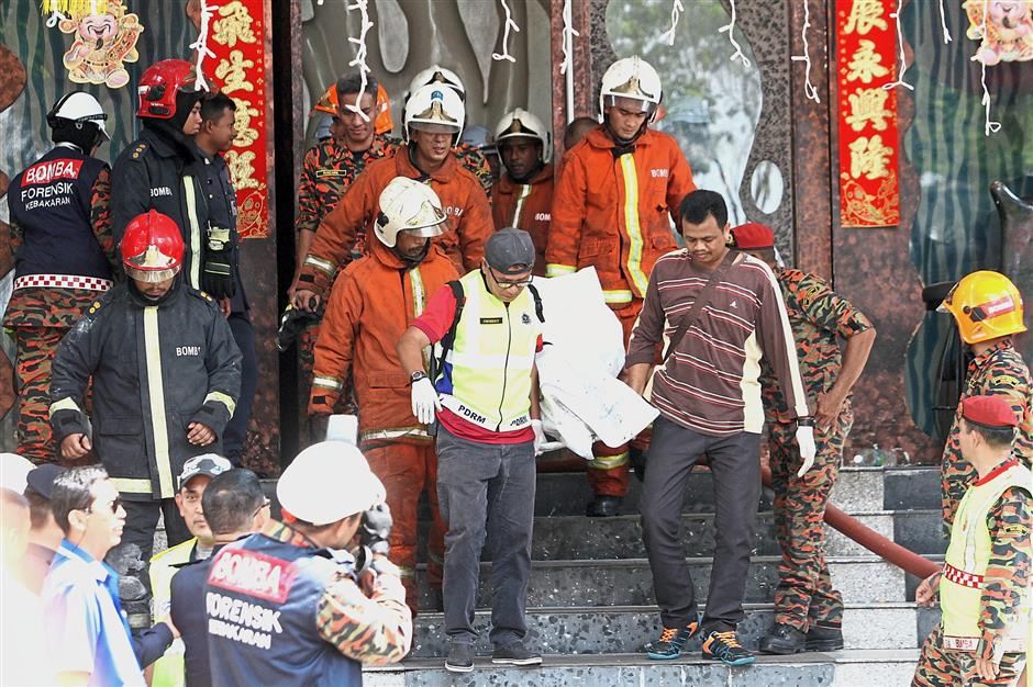 Grim task: Fire and Rescue Department personnel carrying out the dead bodies from the entertainment outlet in Jalan Raja Dr Nazrin Shah, Ipoh. (Right) Family members of the deceased broke down after hearing the bad news.