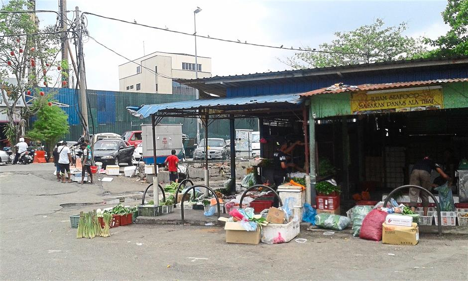 Convenient spot: Baskets of vegetables and fruits placed outside food stalls in Selayang. Mohd Azizi says it is hard to catch the illegal traders in the act of selling these items as some would hide in the stalls when the authorities conduct raids.