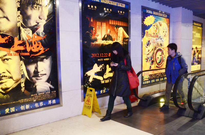 A Chinese woman walks past film advertisements at a cinema in Beijing. Chinese cinemas raked in 21.77 billion yuan in 2013, up 27.5% from 2012 - AFP Photo.
