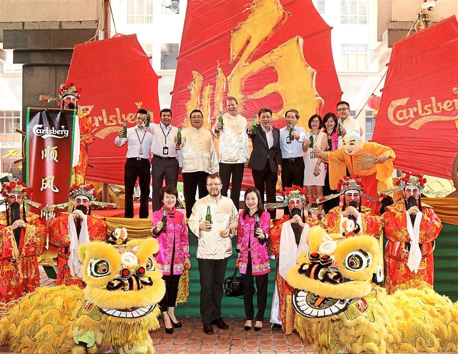 Here's to a prosperous 2015: Wong (on stage, fifth from left) and Andersen (on stage, fourth from left) with other senior management staff of Star Publications (M) Berhad and Carlsberg Malaysia.