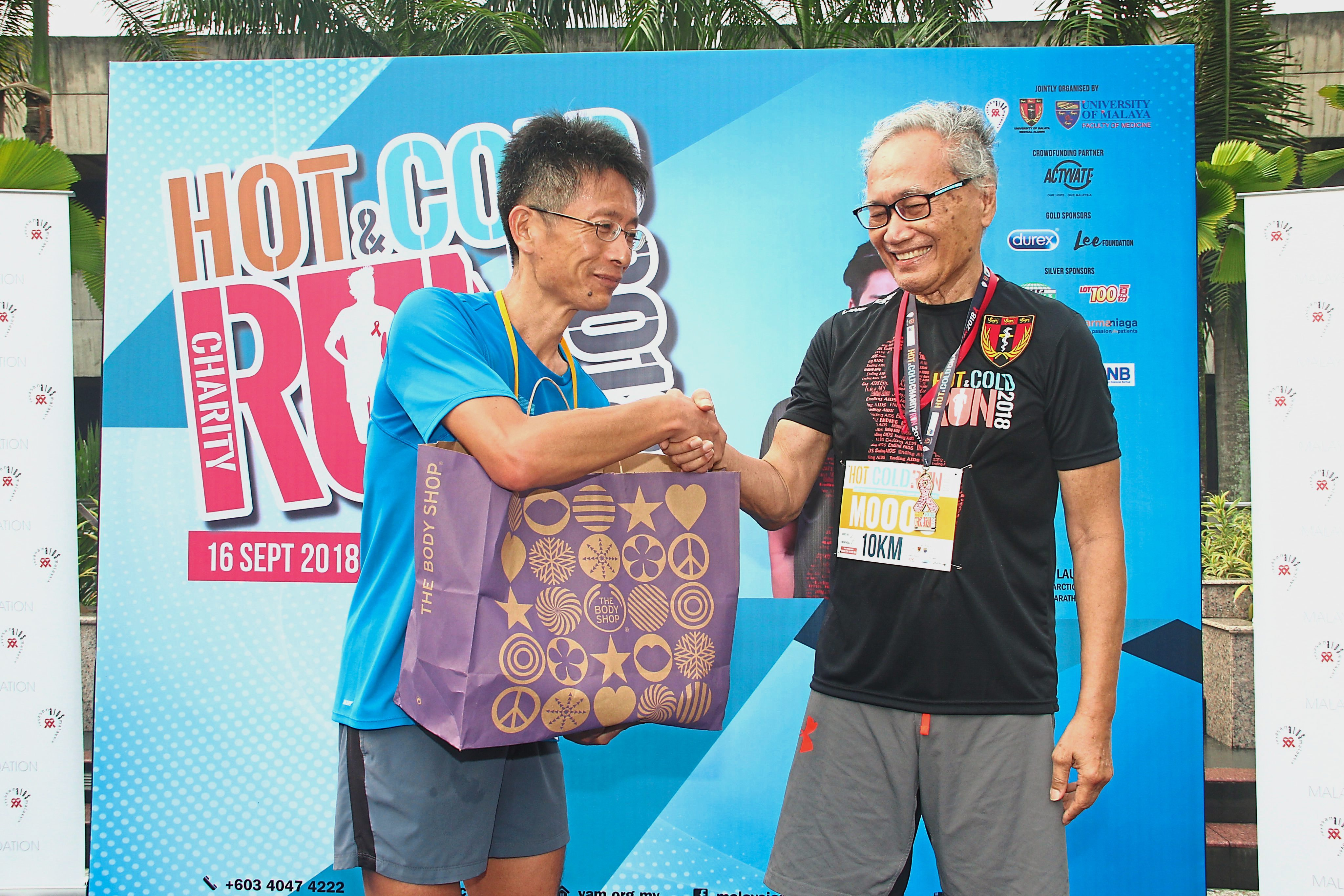 (Below)Dr Khairuddin (right) presenting the top prize to the winner of the 10km Male Runner category.
