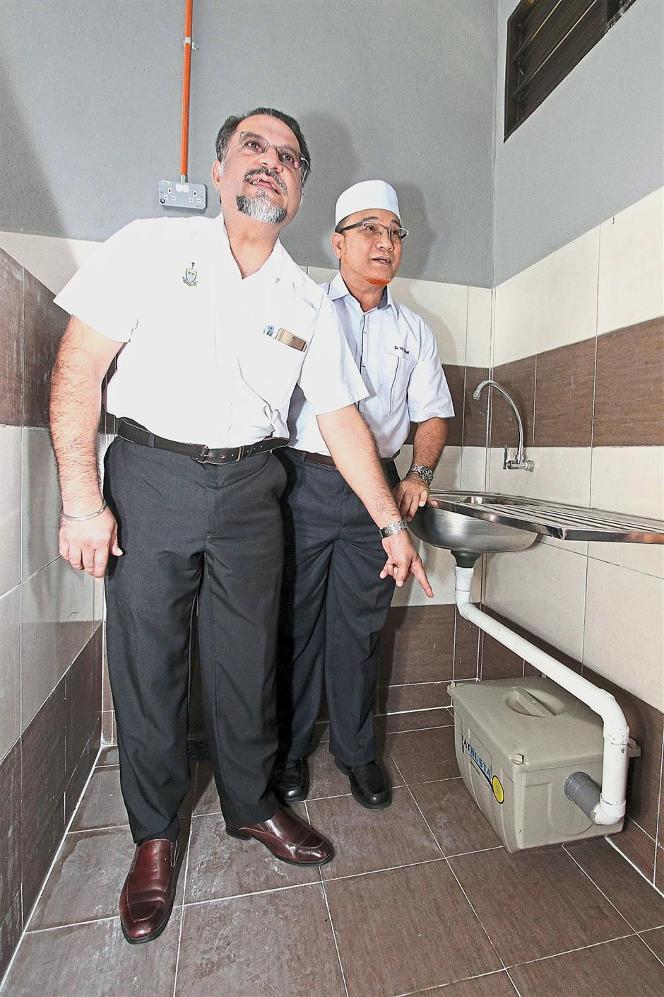 State Housing, Town, Country Planning and Local Government Committee chairman Jagdeep Singh Deo (left) and Seberang Prai Municipal Council (MPSP) president Datuk Rozali Mohamud showing the grease trap installed under a sink at the food stall complex in Sri Penanti Market in Bukit Mertajam on Sept 30, 2018. / star pic by LO TERN CHERN / The Star / Sept 30, 2018.