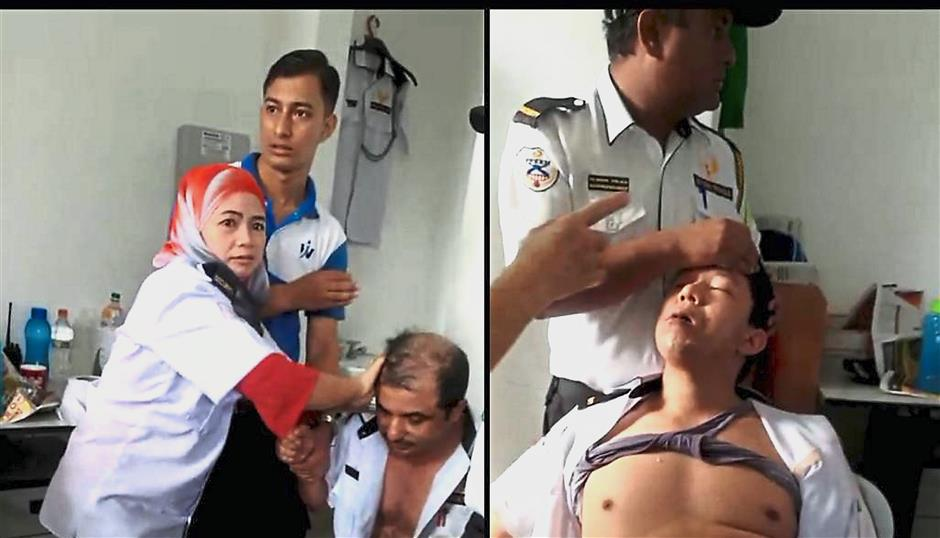 Unfortunate incident: A screenshot of the video showing security guards Bishnu Shrestha (right) and Sapkota Mangal Prasad being helped by their friends (from left) Hasmah, Chandra Khadka and Budhathoki Bhakta Bahadur during the incident at a condominium in Pulau Tikus.