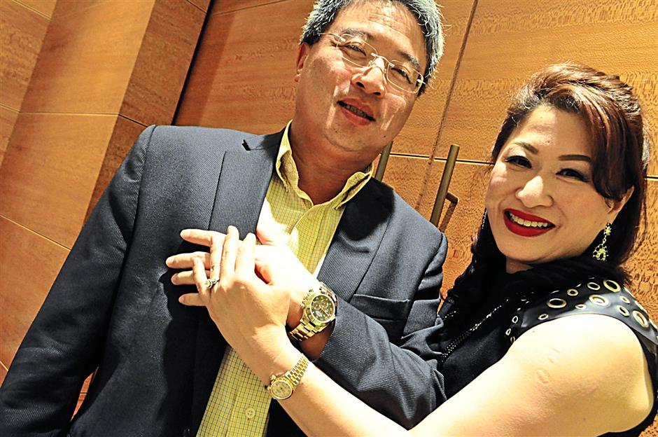 Andy and Adeline Khoo showing their Rolex watches at the cocktail party by the brand at its boutique in Pavilion Kuala Lumpur.