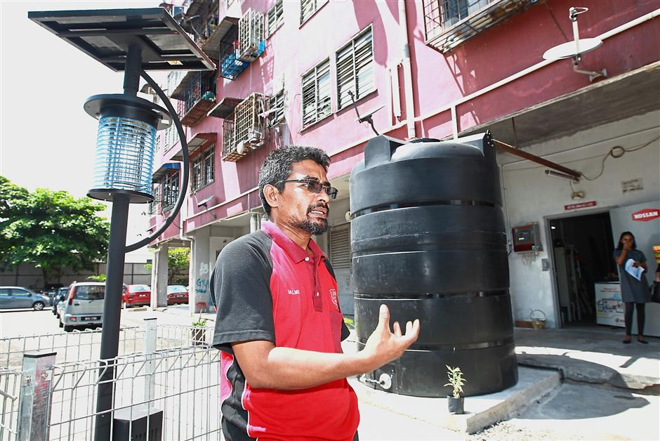 Resident Baharuddin Sulaiman will be among those who will be part of the rain water harvesting project initiated by the Spark Foundation. Behind him is the 72,000 litre water tank installed in Desa Mentari Block 1.