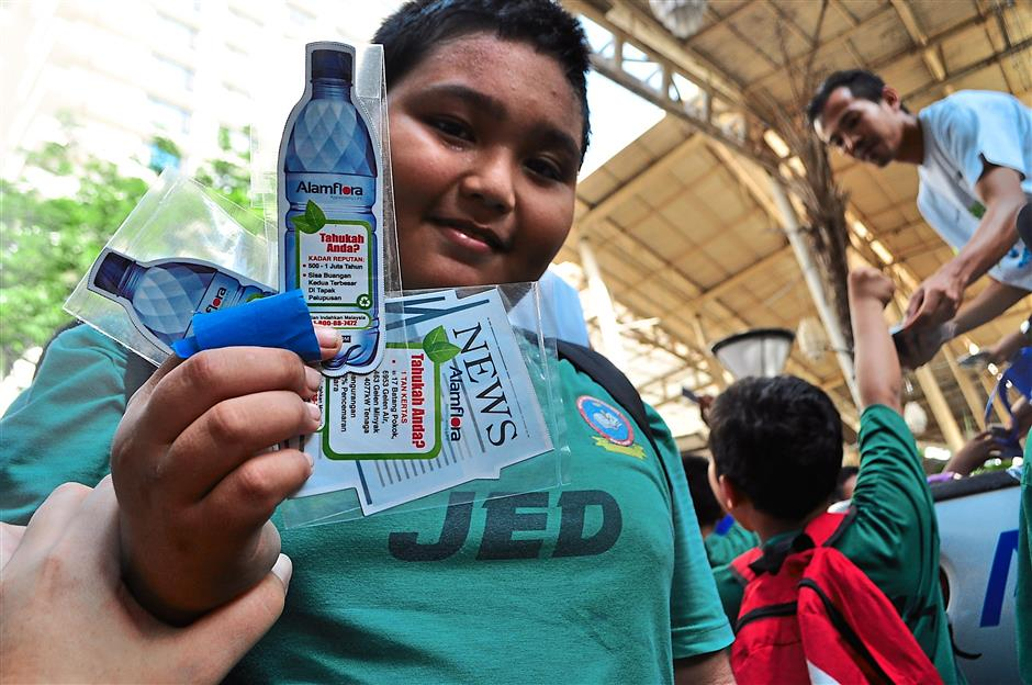 Teach the young: A pupil showing the stickers given by Alam Flora's Eco Rangers who are advocating the importance of reduce, reuse and recycle.