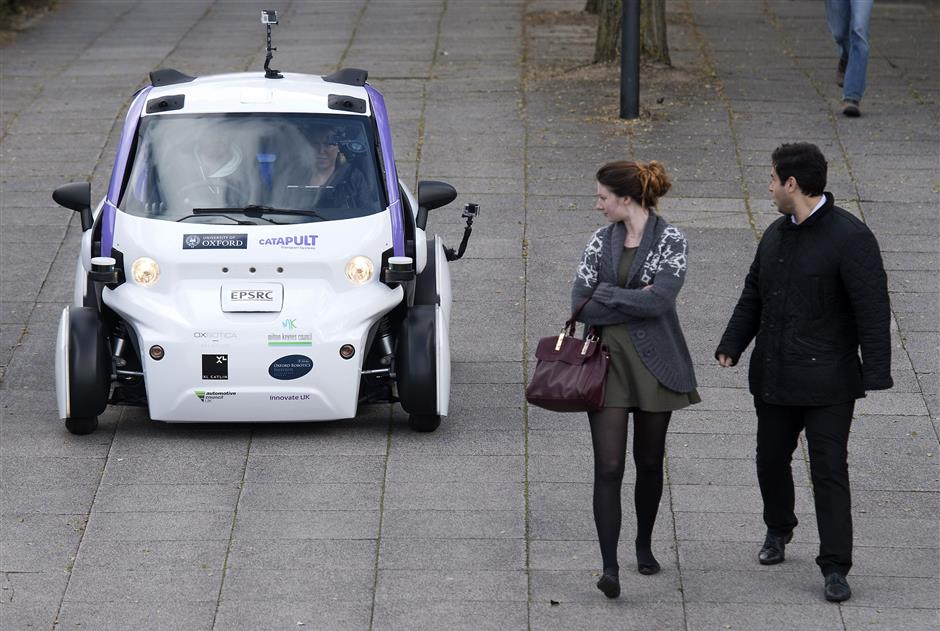 People look towards an autonomous self-driving vehicle, as it is tested in a pedestrianised zone, during a media event in Milton Keynes, north of London, on October 11, 2016. Driverless vehicles carrying passengers took to Britain\'s streets for the first time on Tuesday in a landmark trial which could pave the way for their introduction across the country. The compact two-seater cars trundled along a pedestrianised zone in Milton Keynes, north of London, in a trial by Transport Systems Catapult (TSC) which plans to roll out 40 vehicles in the city. / AFP PHOTO / JUSTIN TALLIS