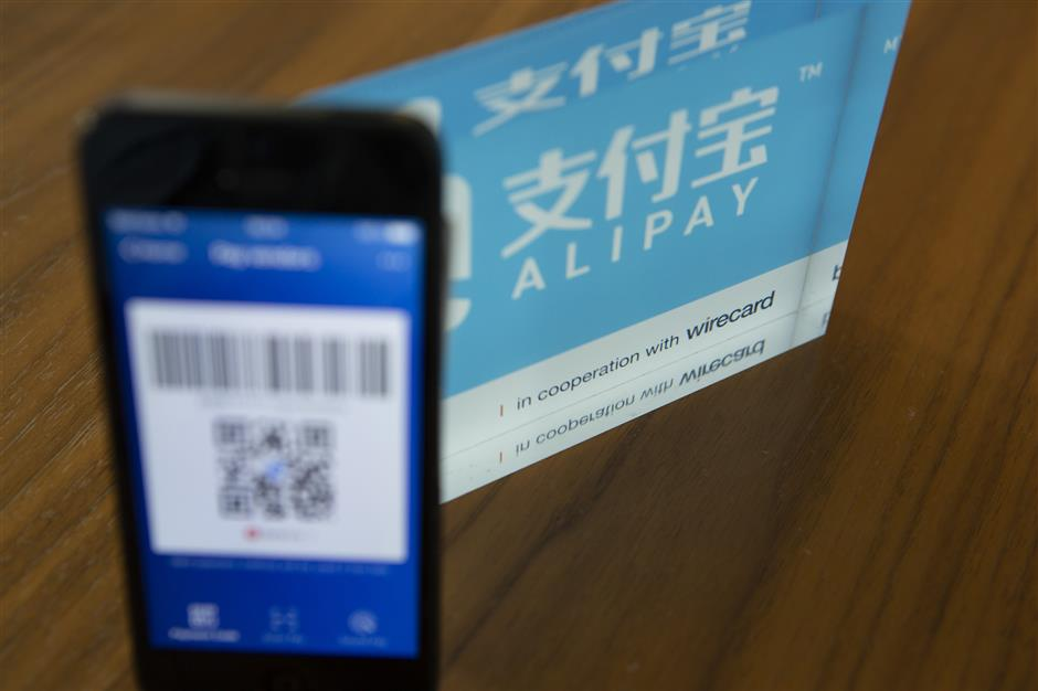 An Alipay digital payment app logo and smartphone sit on a desktop at the Wirecard AG headquarters in Munich, Germany, on Wednesday, Sept. 5, 2018. Commerzbank AG, part of the DAX Index stock gauge since its inception in 1988, will be replaced by fintech company Wirecard AG, index provider Deutsche Boerse AG said in a statement late on Wednesday. Photographer: Matthias Doering/Bloomberg