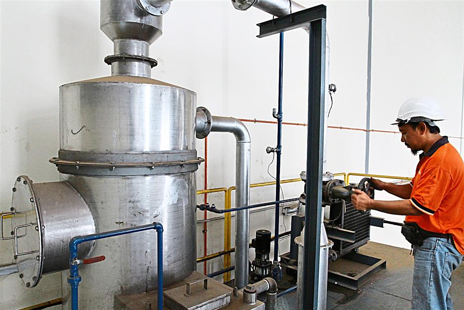A technician adjusting the air flow control valve to tune the pressure in the pilot unit process drum of the  Carbonator waste treatment system.