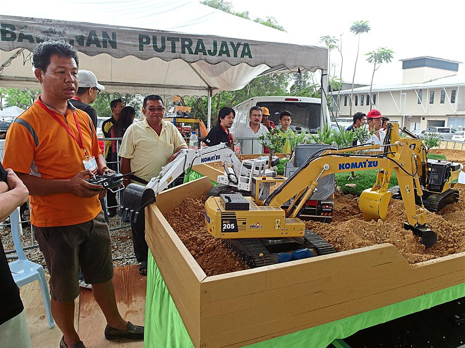 Fong Yat Seng (right) using remote control to move an excavator which he constructed himself, in the RC Truck and Construction Equipment category.