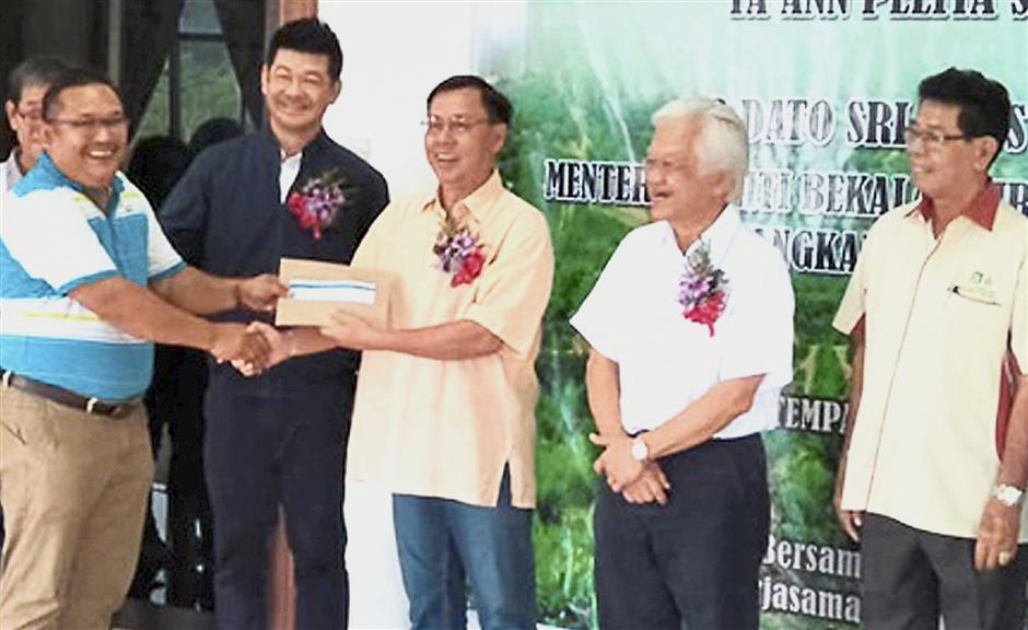 A recipient receiving the dividend from Dr Utom (third from right) while Abdul Hamed (second from right) and others look on.