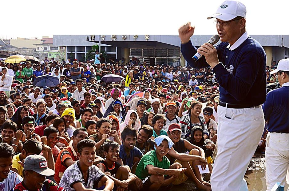 David Liu led the advance Tzu Chi disaster relief team after the Yolanda hurricane last year. Here he is seen (right, with microphone in hand) rallying the victims in Tacloban before starting cleanup of their homes.