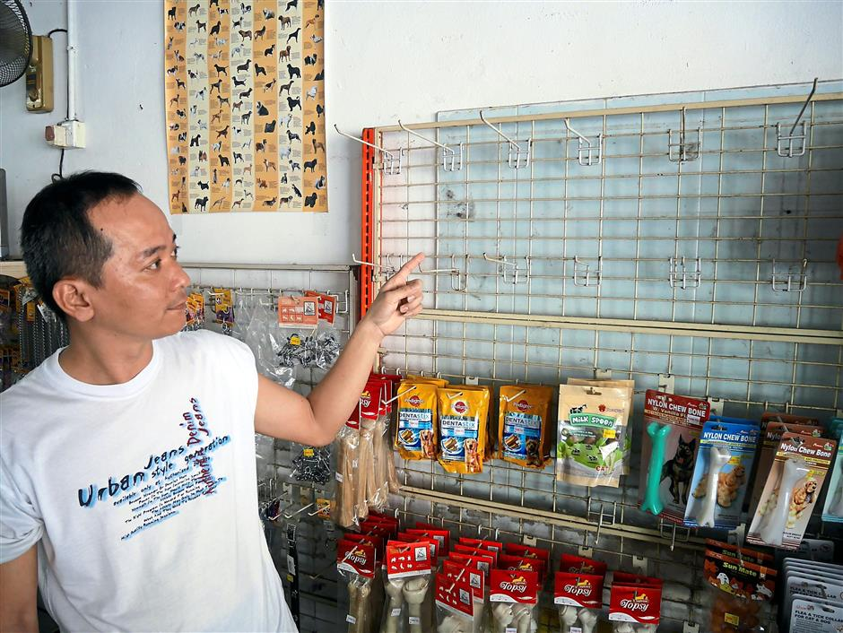 Puan pointing at an empty rack previously occupied by a variety of pet toys, which have been discontinued, in his shop in Taman Ipoh Jaya.