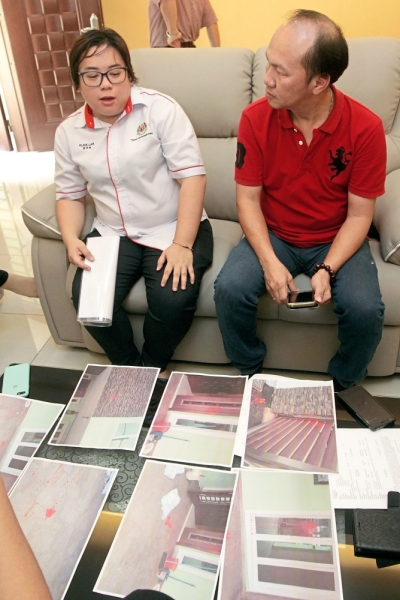 Lan (left) discussing with Low after his house was splashed with red paint.