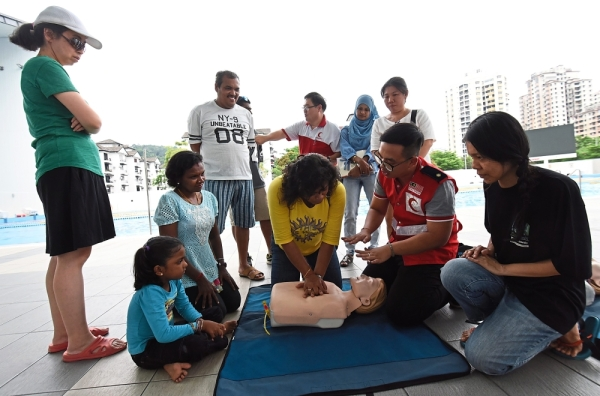 Malaysian Red Cresent Society member Benny Lee (second right) conducting a CPR training session with some of the parents.