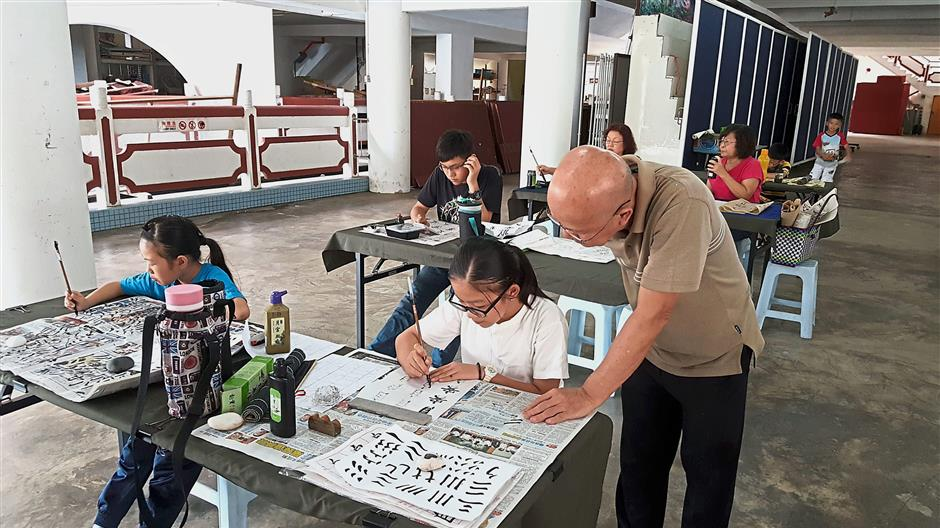 Students learning Chinese calligraphy at the Pahang Buddhist Association.