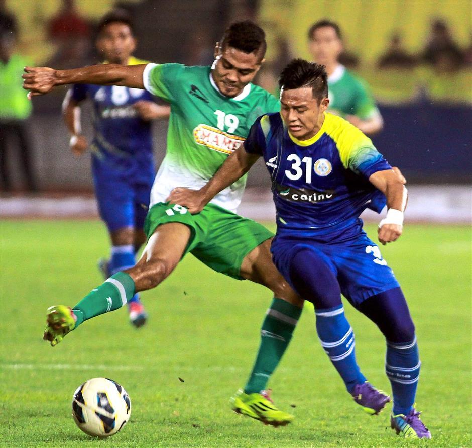 Malacca's Nurshamil (left) involved in a tussle for the ball with Perlis' Mohd Syafiq Azmi.