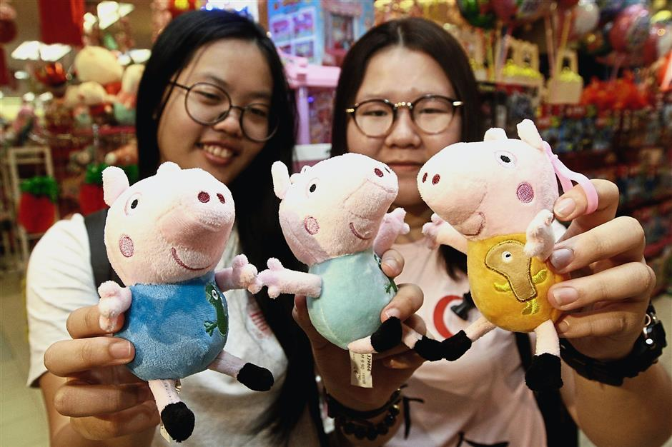 Lim Jia Xin, 19, (left) and Tan Zhing Yee, 20, showing the Peppa Pig soft toys for sale at Prangin Mall.