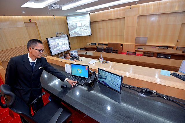 High Court deputy registrar Khairi Haron showing the two computers on the Construction Court judge's table - the one on the right shows the same image as that on the interactive white board at the back and the one on the left is for her to make her own notes. Just below the judge's table is interpreter Zamarullah Md Nur who controls the images on the white board as required during the examination and cross-examination of witnesses in the high-tech equipped courtroom at Jalan Duta.