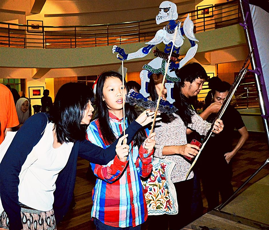 Fans eagerly gather round the centre stage to have a closer look at the re-interpreted puppets, modern figures done up in classic Kelantanese wayang kulit style, with Sangkalah Vedeh receiving a lot of attention.