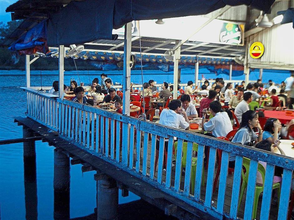 Customers enjoying seafood dishes at a restaurant near the Bukit Tambun jetty.