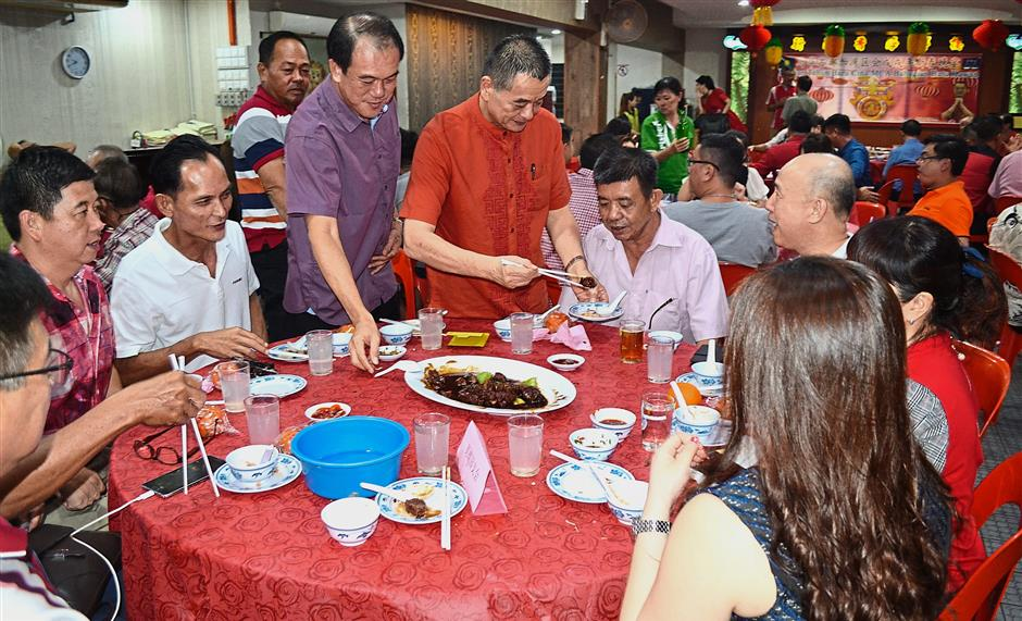 Teik Cheng (centre in red) with Lee Huat on his right, and other members tossing the yee sang. (Top) Teik Cheng and Lee Huat serving food to a guest at the dinner held in conjunction with Chinese New Year.