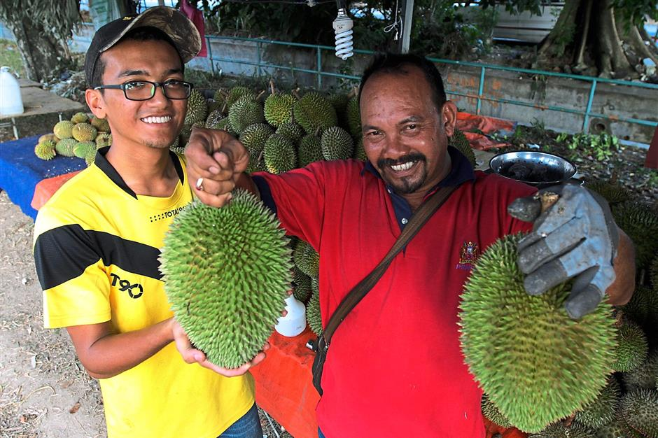 """Mohamad Abdul Samad (right) and his son holding the """"Durian Jantung"""" species - so named because of the heart shape the breed has."""