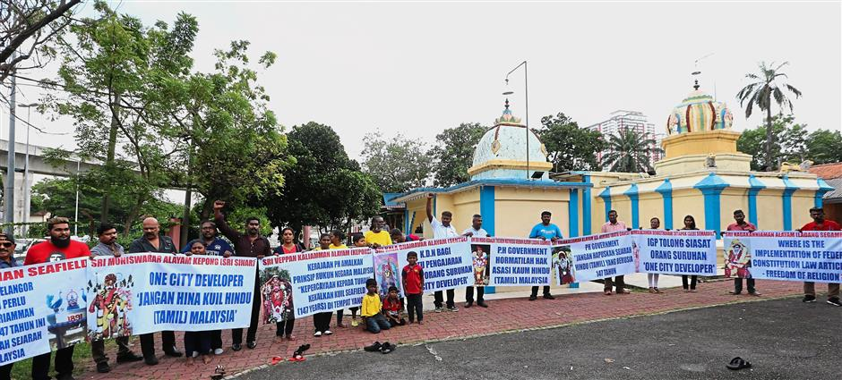 Making a stand: Protesters holding placards seeking justice during a rally at the Seafield Sri Maha Mariamman Temple.