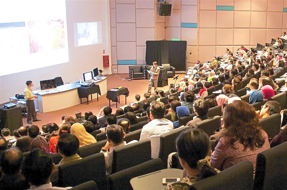 Attentive: Participants listening to a presentation on multimedia technology at the Swinburne Sarawak lecture theatre.