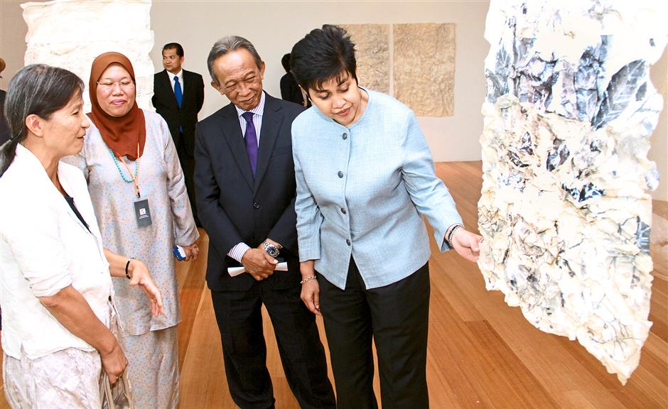 (From left) Sprunt, Malaysian Watercolour Society patron Tan Sri Samsudin Osman and Nor Shamsiah admiring one of the artworks at the exhibition.