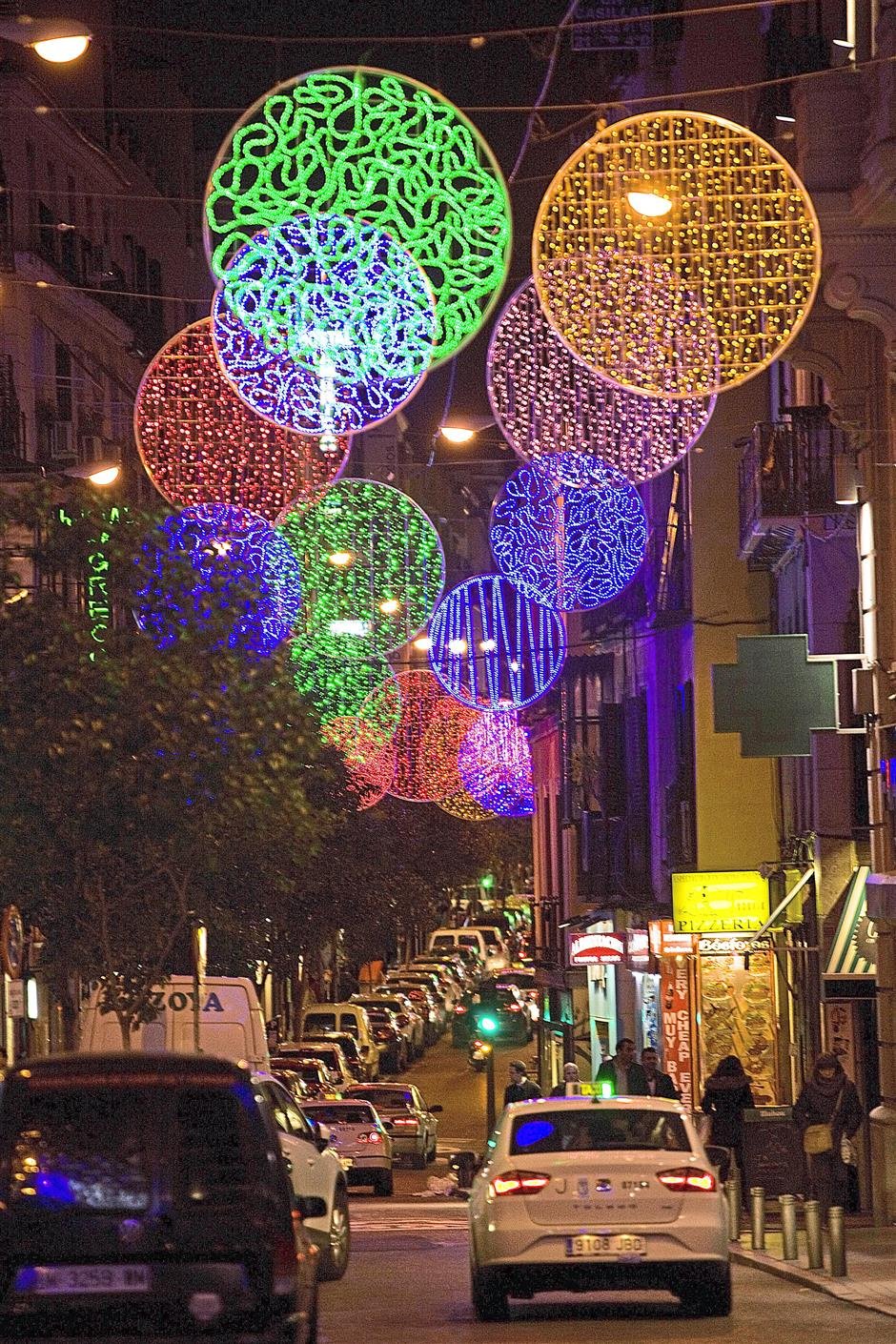 A taxi passing under the Christmas lights illuminating Hortaleza street, in the district of Chueca near Gran Via in the centre of Madrid, Spain. — AFP