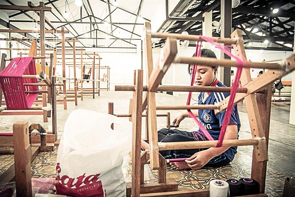 The company's aim is to have trainees skilled enough to work at their own looms in six months.