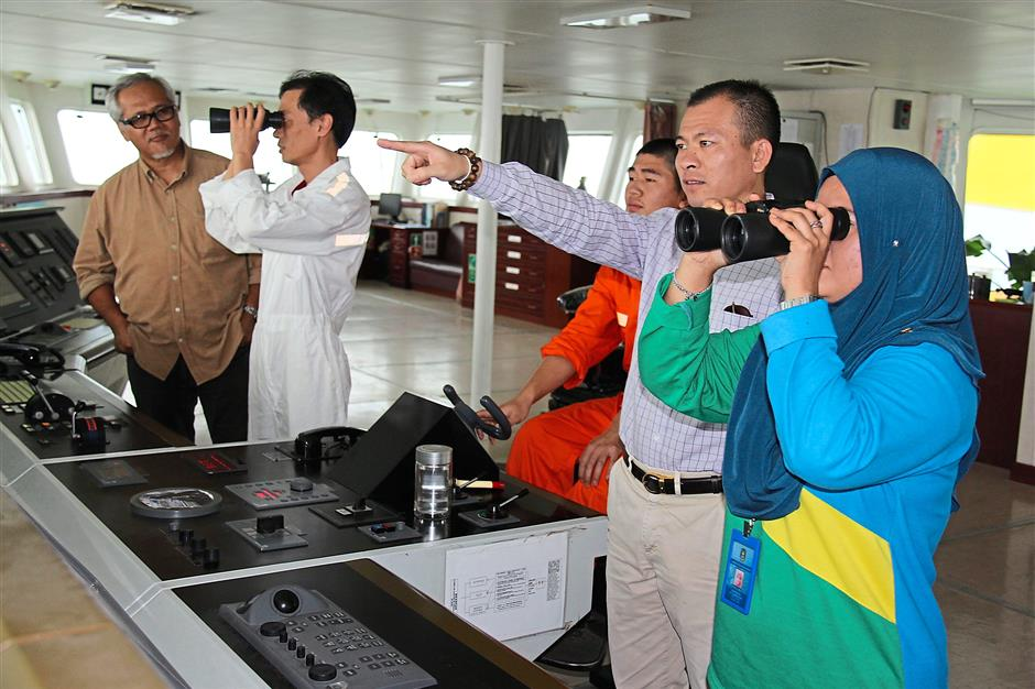 Norfaezah (right) looking through binoculars as Xue (second from right) points to other ships in the area while on-board the TSHD Xin Hai Feng vessel.