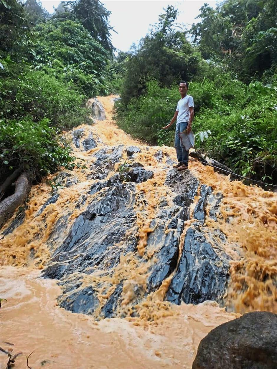 Polluted water: A villager showing a teh tarik-coloured river allegedly caused by illegal logging in Gunung Inas, Kedah.
