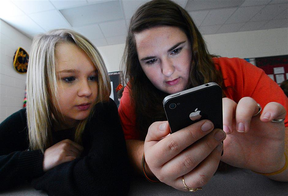 FILE - In this March 13, 2014, file photo, Hartselle High School students Lissa Blagburn and Brantlee Wright use an iPhone as they work on a networked lesson in Spanish class in Hartselle, Ala. Teachers say they're seeing so much student anxiety that a national union newsletter labels it a 'mental health tsunami.' Many of those educators, along with doctors and researchers, say smartphones, especially the nonstop pull of social media, are at least partly to blame. Schools are starting to react. (Gary Cosby Jr./The Decatur Daily via AP, File)