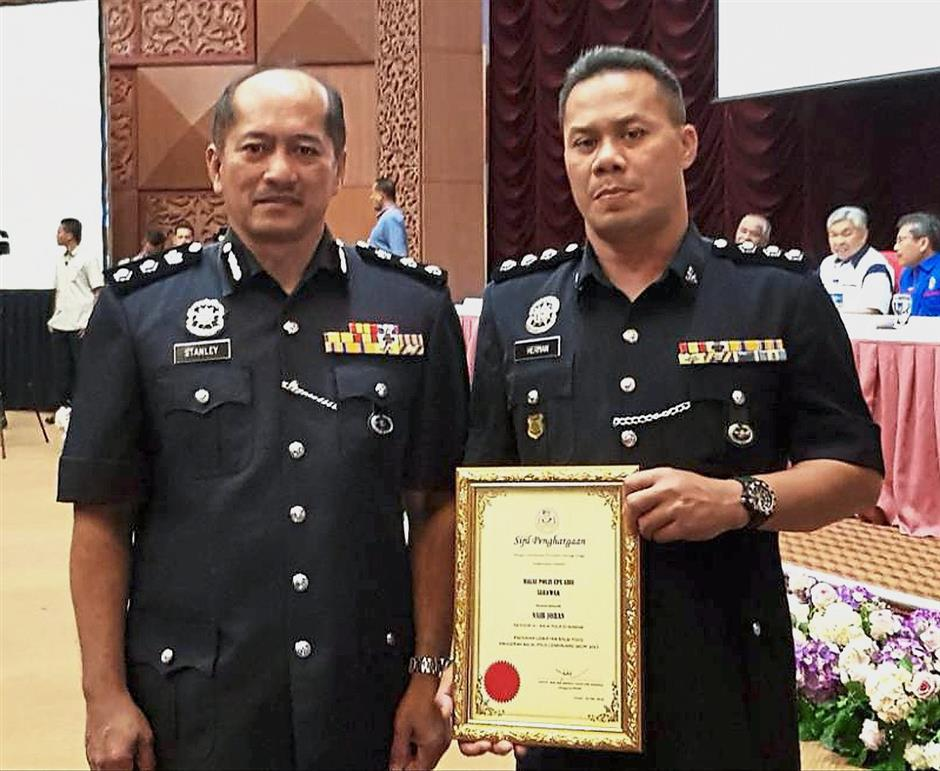 ACP Stanley (left) and ASP Herman showing the award certificate.