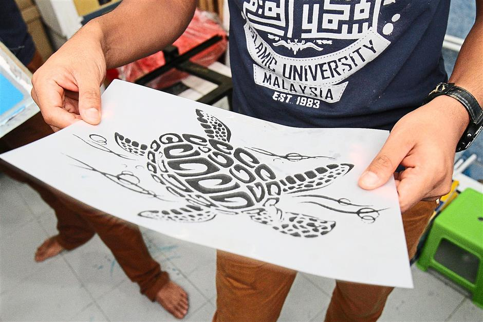 Original copy: Asyraf takes a hour to transfer a design onto a silk screen before they proceed with the printing process.