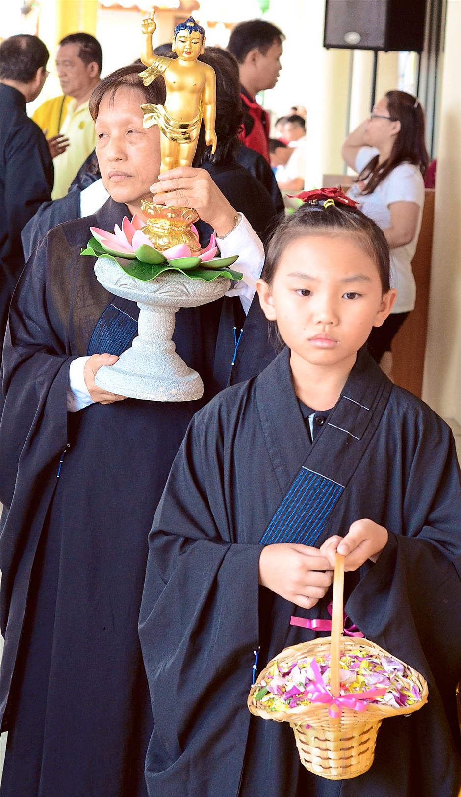 Observance: A young devotee carrying flowers to be sprinkle at the ceremony.