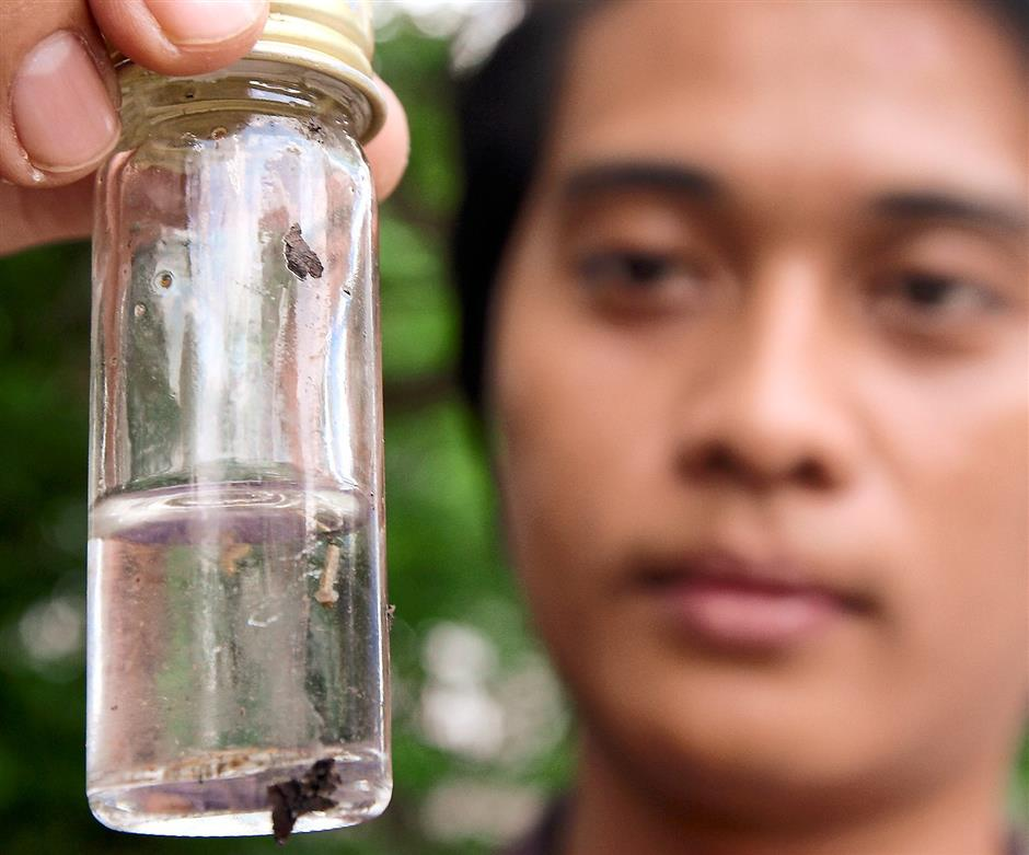MBPJ Health and Environment staff shows a jar of mosquito larvae collected outside Park 51 Residency off Jalan 51A Petaling Jaya.