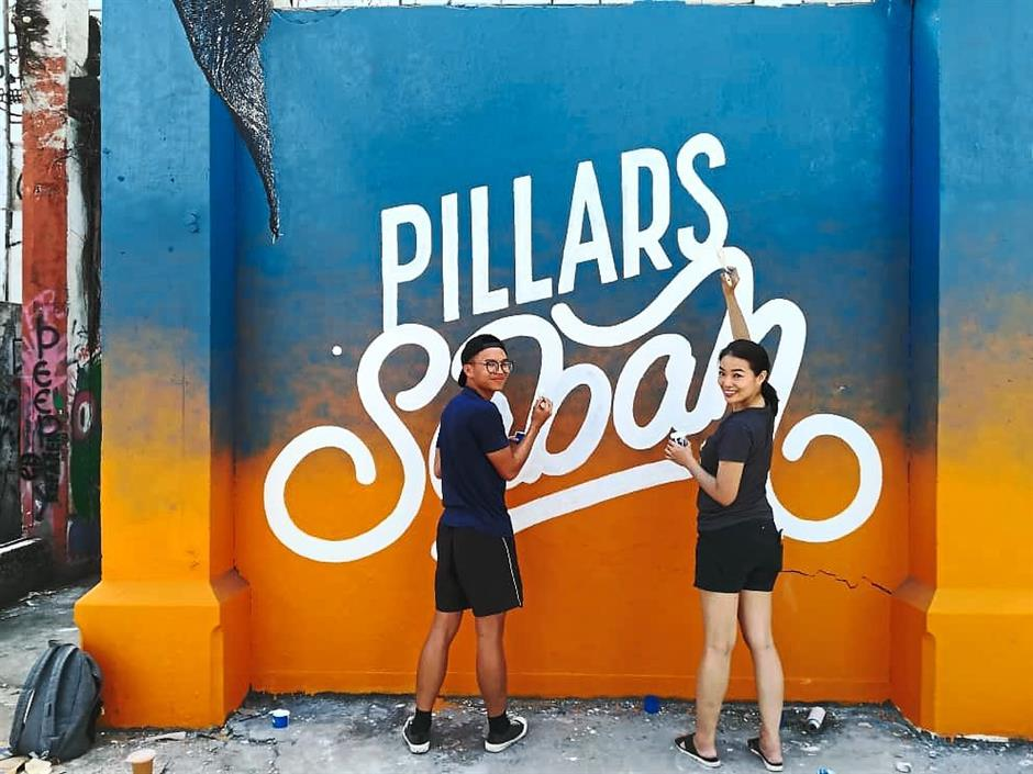 Artist Wilson Ng and Red painting the Pillars of Sabah mural at the Sabah Street Art Gallery. The mural was inspired by Sabahs sunset, which Red described as one of the best sunsets in the world.