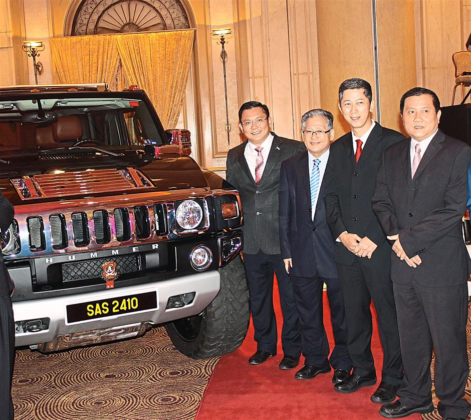 Ch'ng (fourth from right), Xian (third from right) and other guests posing next to the Hummer vehicle that was presented to the Sultan for his birthday.