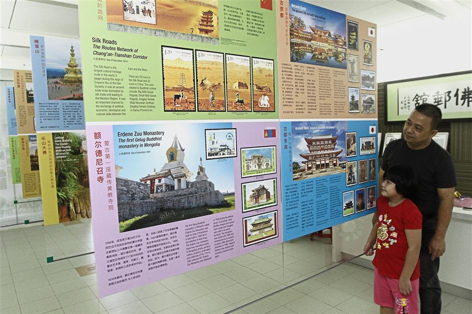 Yeoh guiding a girl on a tour of the exhibits at the gallery.