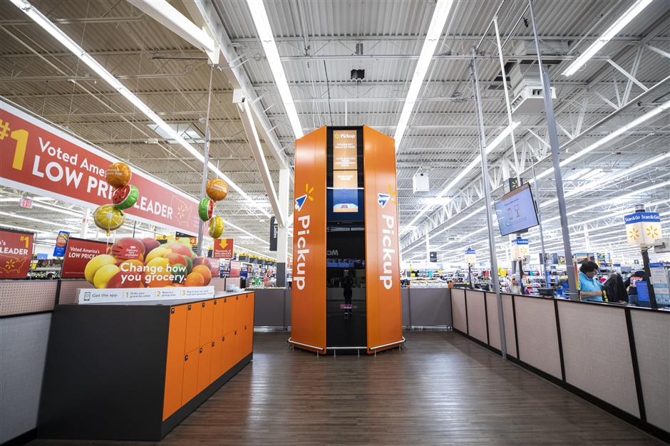 The pickup tower in the Bonney Lake Walmart is a tall, newly installed orange beacon, beckoning online shoppers to unlock their purchases inside. It's manually loaded by Walmart crew members after a shopper places an order. Larger orders are placed in the lockers to the left or kept in the back. The tower activates upon approach and opens when the shopper scans their mobile device. The upgrades are part of a $36 million investment in new technologies and upgrades to Walmarts in Washington state (Bettina Hansen / The Seattle Times/TNS)