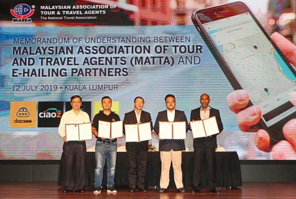 (From left) Ong, Lim, Tan, Hynol Hakim and Kumeran at  the signing of the MOU between MATTA and four e-hailing companies.