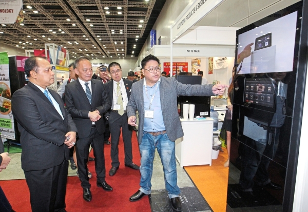Chua (second from left) and Zulkefli (left) visiting some of the exhibitors' booths at the launch of the 20th Malaysian International Food and Beverage Trade Fair.