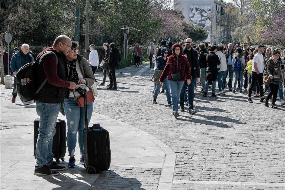 A couple of tourists look for their Airbnb accomodation in the Koukai area of Athens on March 22, 2019. - According to Airbnb data, there are over 8,000 apartments for rent in central Athens alone, at an average of 67 euros per night, including some 1,200 flats in districts close to the Acropolis. About half are multi-listings by owners with more than one property online, Airbnb says. Among them are a few hundred foreigners -- mainly Chinese, Russians and Israelis -- who tapped into a golden visa programme introduced in 2013 for property purchases over 250,000 euros ($285,000), says Lefteris Potamianos, head of the Athens real estate association. (Photo by LOUISA GOULIAMAKI / AFP)