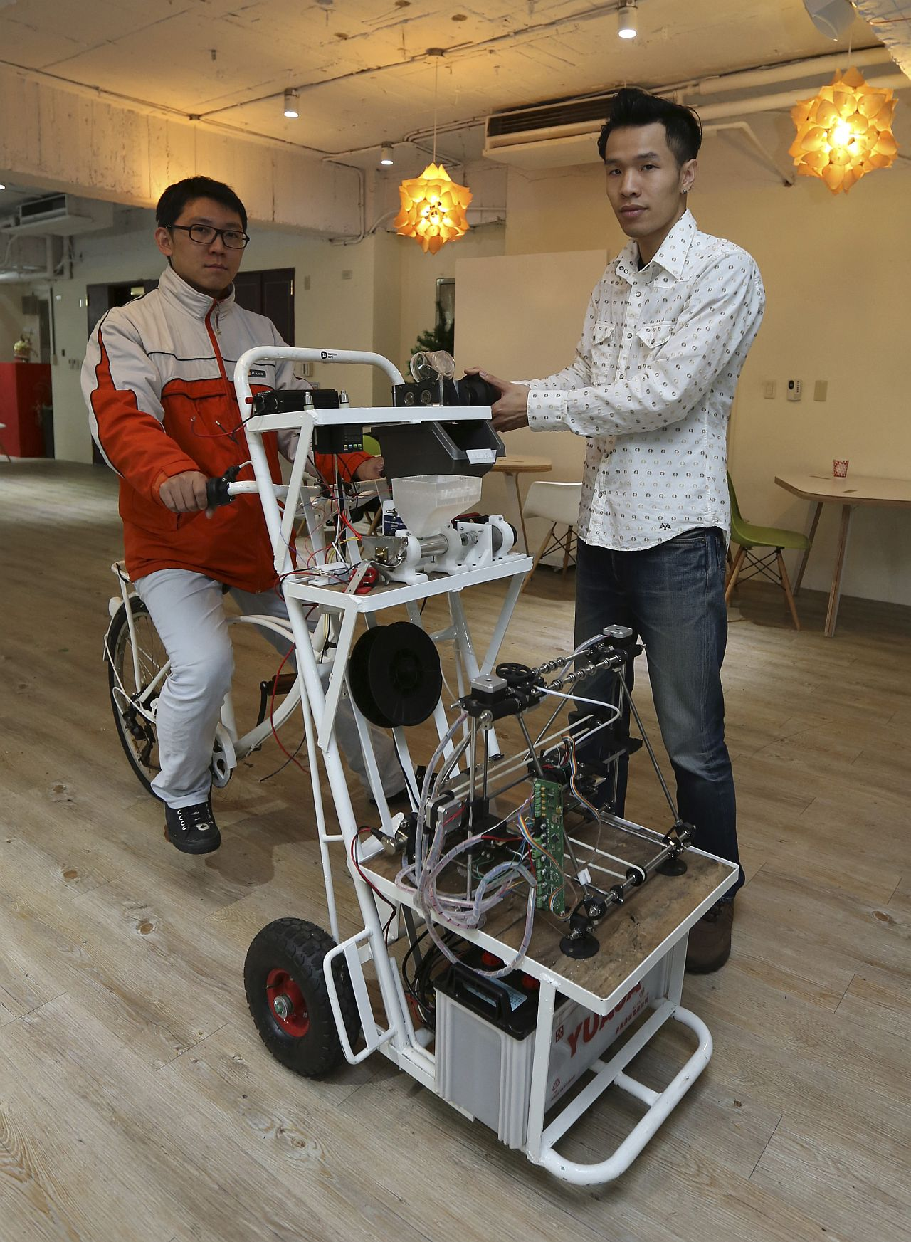 COOL CONTRAPTION: Kamm Kai-yu (right), co-founder of boutique design studio Fabraft, displaying a bicycle with a 3D printer installed in front, in Taipei. — Reuters