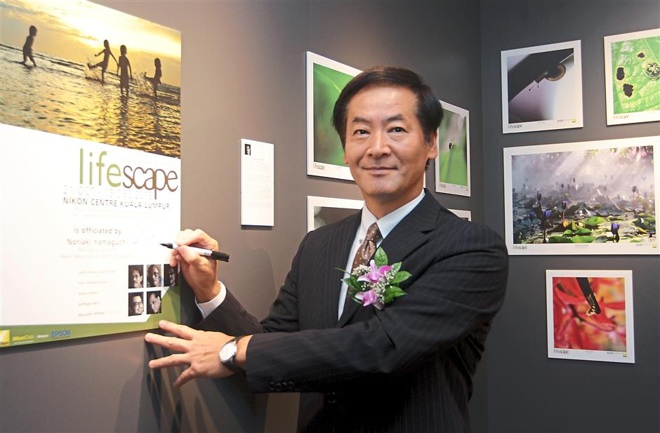 Yamaguchi signing a plaque at the launch of the new Nikon centre.