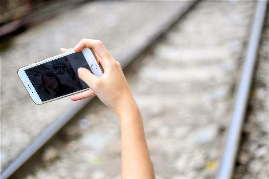 This photograph taken on June 8, 2019 shows a woman posing for a selfie on the railway track in Hanoi\'s popular train street. (Photo by Manan VATSYAYANA / AFP)
